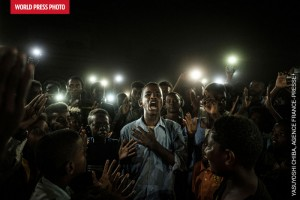 """En couverture du catalogue du World Press Photo 2020, la photo 1er Prix : """"Une Voix dans le Noir"""", un jeune homme récitant un poème pour la liberté et le retour à un régime civil, à la lumière de téléphones portables, lors d'une manifestation à Khartoum en 2019©Yasuyoshi Chiba, Japon/AgenceFrance-Presse"""
